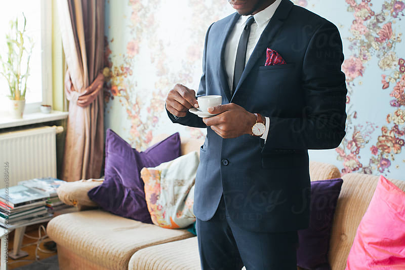 Standing Black Man in Elegant Suit Drinking Espresso in Bright Living Room by VISUALSPECTRUM for Stocksy United