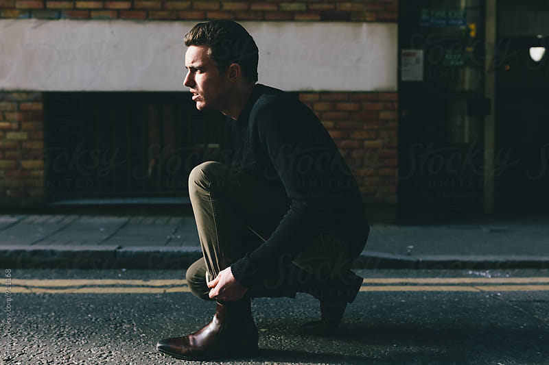 Man Tying Boots in the Street by HEX . for Stocksy United