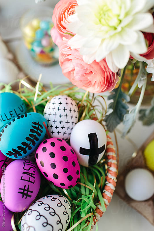 Easter eggs in a basket next to fresh floral blooms by Kristen Curette Hines for Stocksy United