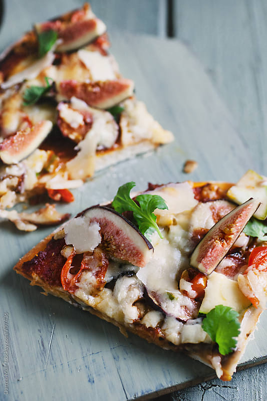 Two slices of vegetarian pizza. by Darren Muir for Stocksy United
