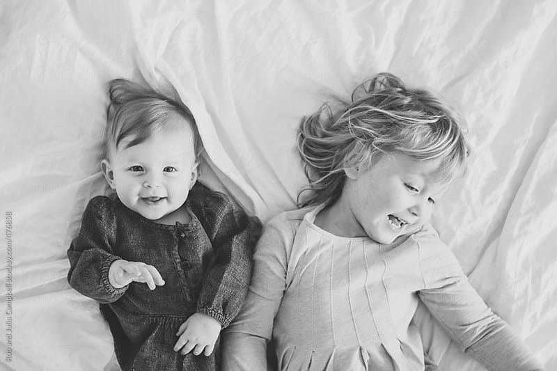 Cute, happy toddler girl and baby sister lying down on soft white bed by Rob and Julia Campbell for Stocksy United