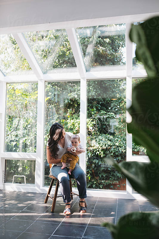 Young mom enjoying holding baby inside sun room by Rob and Julia Campbell for Stocksy United
