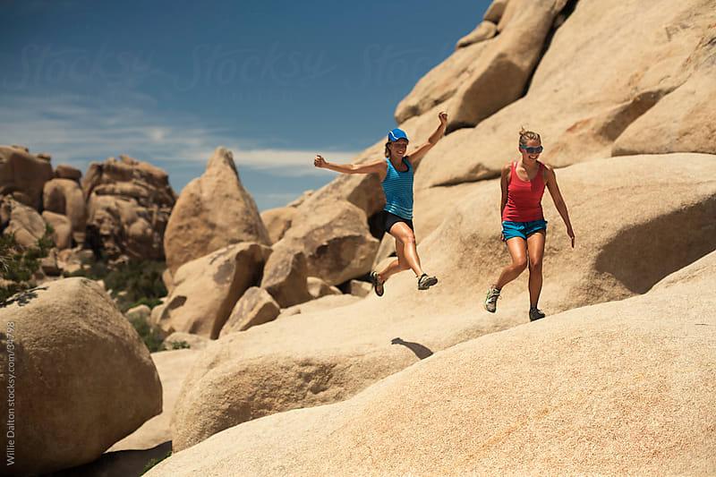 Two Women Jump Across Rock by Willie Dalton for Stocksy United