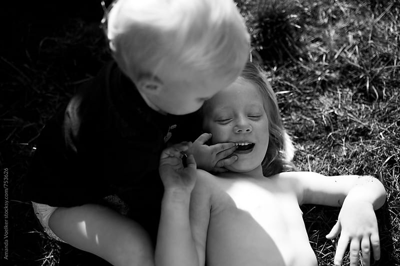 Little Girl Plays with her brother on the Grass in the bright sun by Amanda Voelker for Stocksy United
