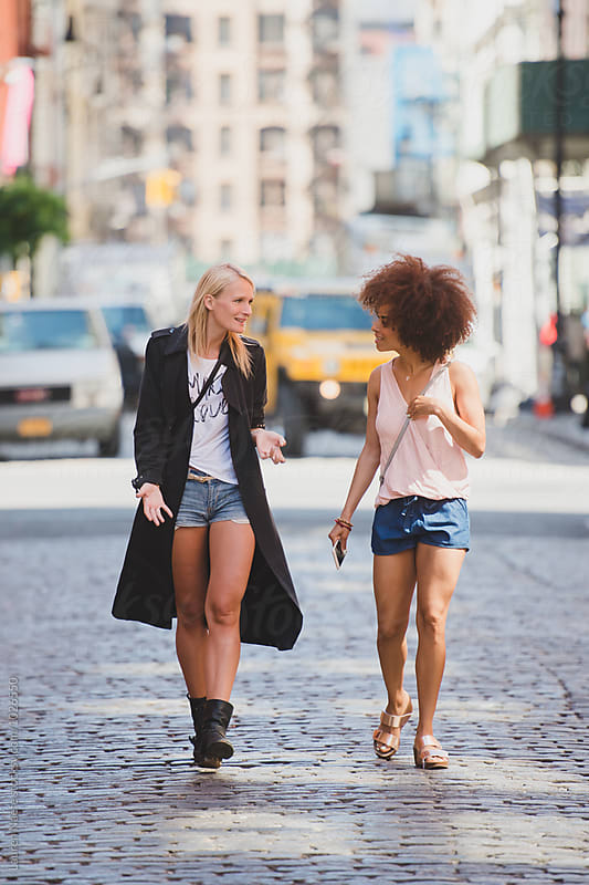 Friends walking on cobblestone in the city by Lauren Naefe for Stocksy United