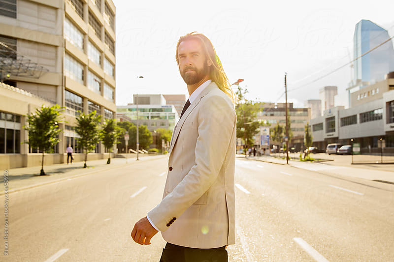 Business man walking across the street by Shaun Robinson for Stocksy United