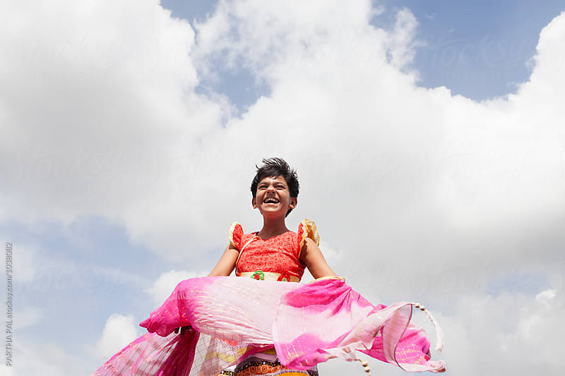 Happy girl laughing with a wonderful sky at backdrop by PARTHA PAL for Stocksy United