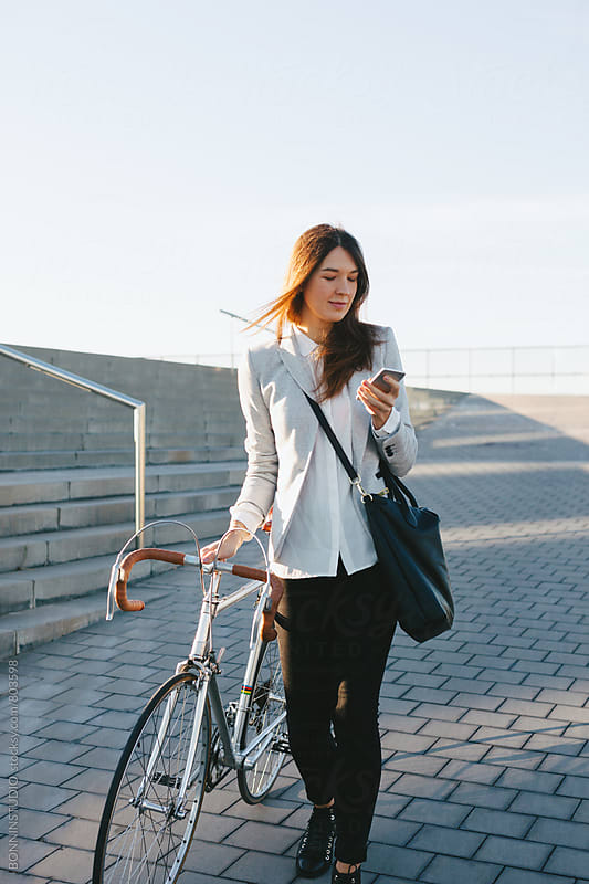 Businesswoman walking with her vintage bicycle whilst using her phone outside. by BONNINSTUDIO for Stocksy United