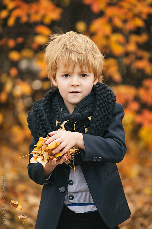 A young boy holding a pile of leaves ready to throw by Ania Boniecka for Stocksy United