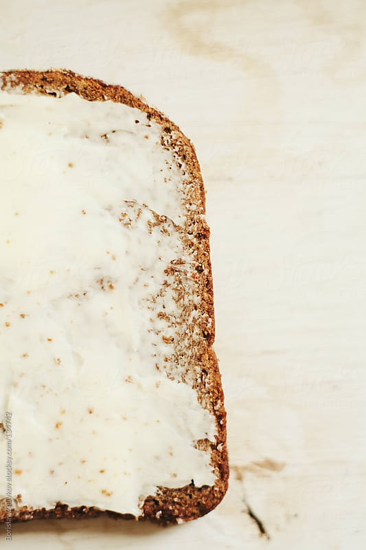 Buttered slice of rye bread on a white wooden surface by Borislav Zhuykov for Stocksy United