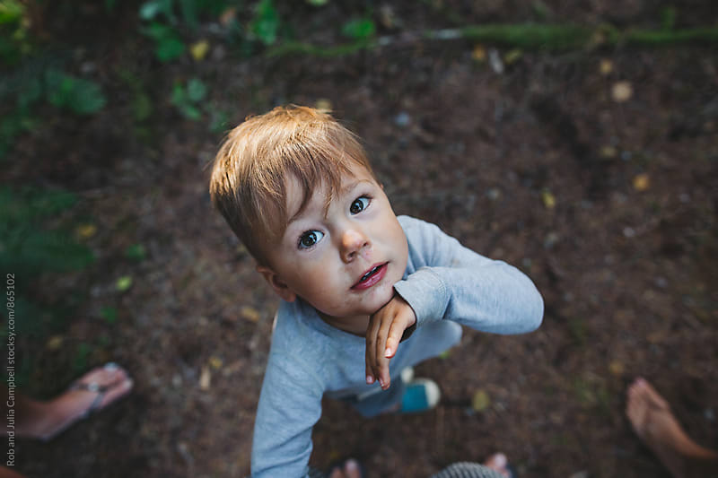 Cute little toddler boy looking up to camera by Rob and Julia Campbell for Stocksy United