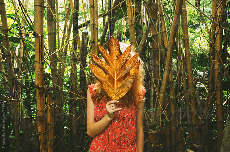 Girl with leaf in front of face by Thomas Shull for Stocksy United