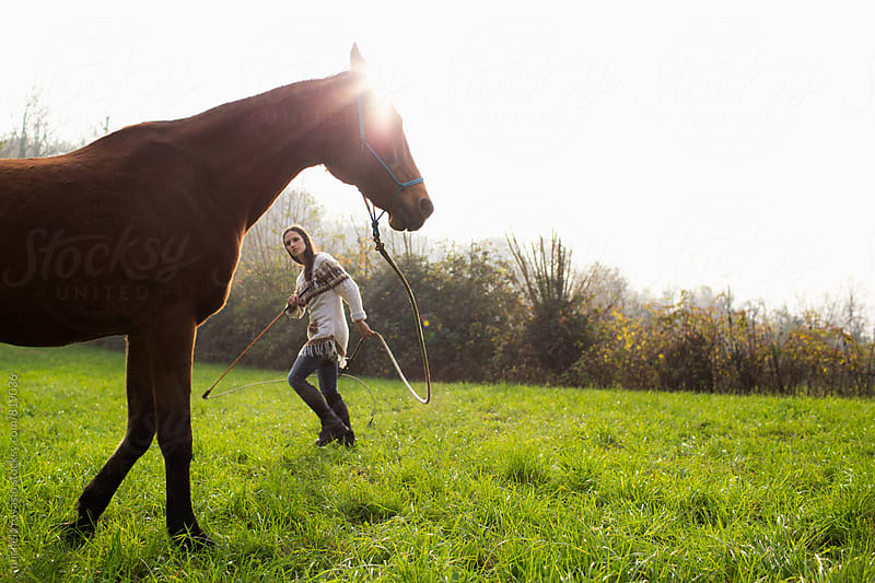 Young woman doing a Natural Horsemanship exercise with her horse by michela ravasio for Stocksy United