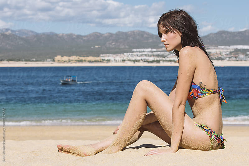 A beautiful model sitting on a beach looking into the distance by Ania Boniecka for Stocksy United