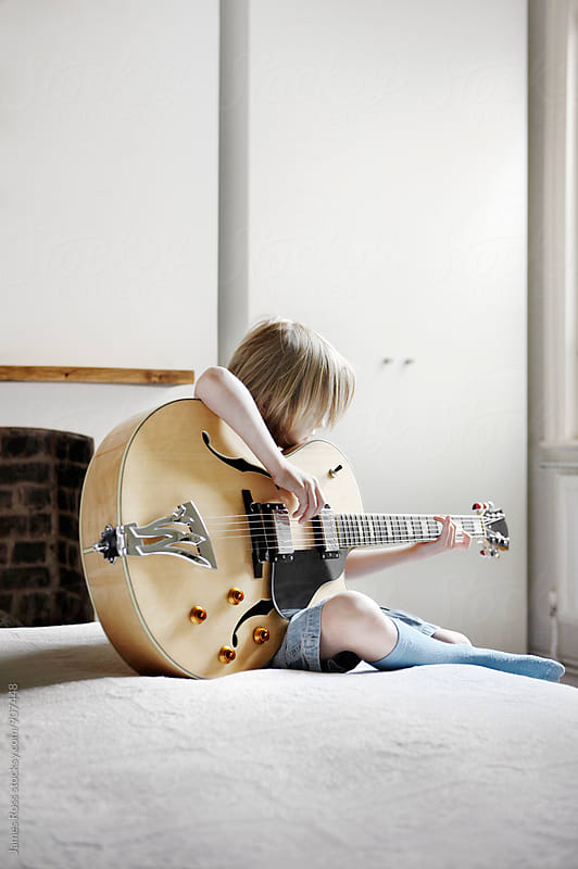 A young boy playing guitar by James Ross for Stocksy United