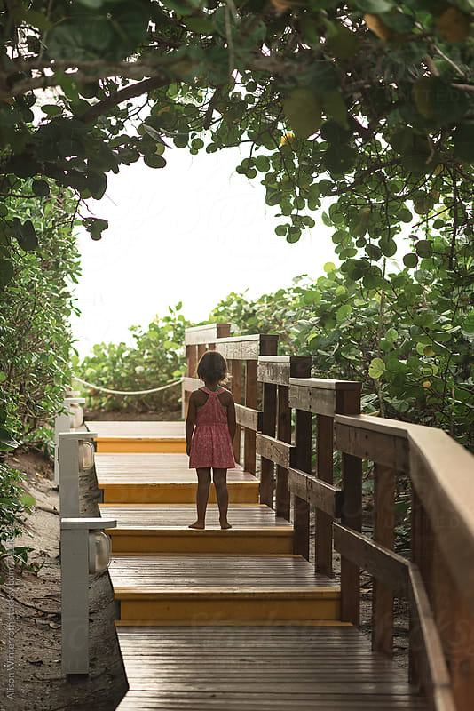 A Child Stands On A Walkway Looking Towards The Beach by Alison Winterroth for Stocksy United