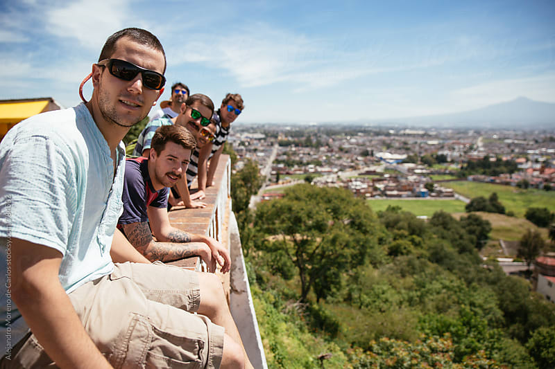 Group of young men leaning on a lookout point with the view of the city and volcano in Cholula in Mexico by Alejandro Moreno de Carlos for Stocksy United