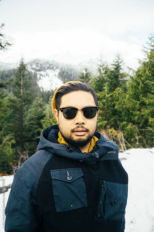 Trendy Young Man With Nose Ring Wearing Classic Sunglasses In Snowy Forest by Luke Mattson for Stocksy United
