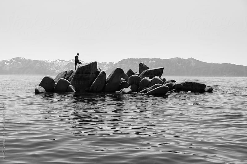Man walking on boulders in the middle of a lake by Amy Covington for Stocksy United
