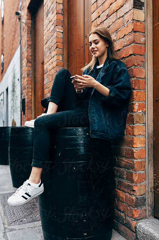 Young woman using a phone sitting in the city by HEX. for Stocksy United