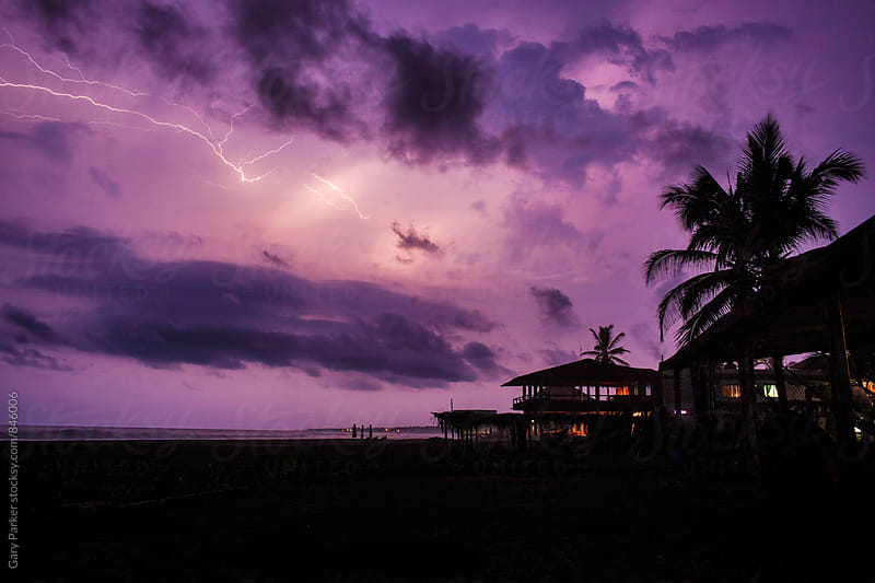 A purple sky lights up with lightning on a tropical Mexican beach by Gary Parker for Stocksy United