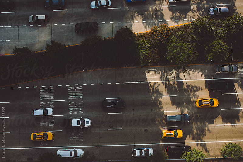Cars moving through traffic by Lauren Naefe for Stocksy United