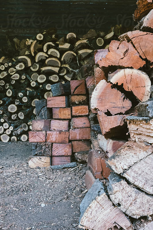 Three types of stacked firewood in a barn by Rowena Naylor for Stocksy United