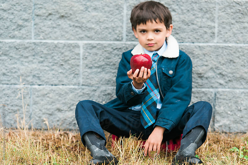 little boy in a school uniform holds an apple on his first day back to school by Tara Romasanta for Stocksy United