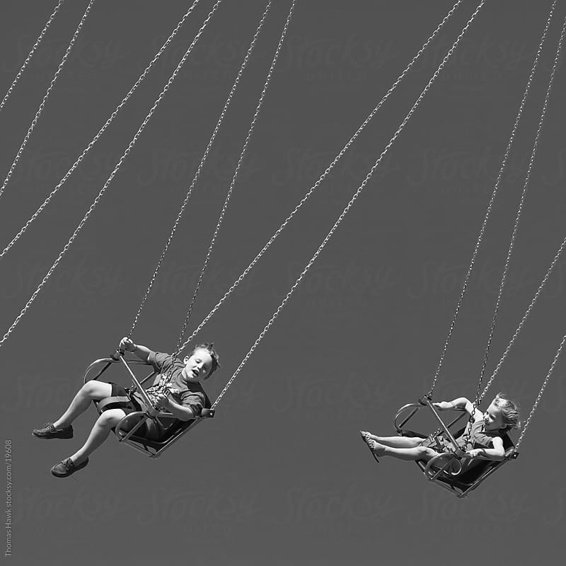 boy and girl on wave swinger ride by Thomas Hawk for Stocksy United