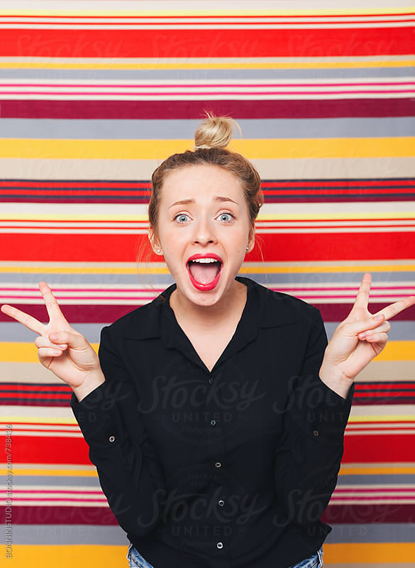 Portrait of a woman making funny faces in front of a striped wall. by BONNINSTUDIO for Stocksy United