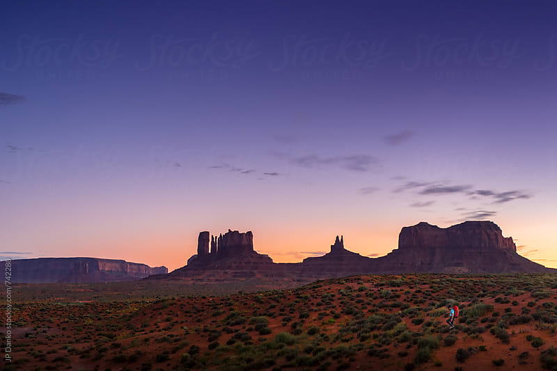 Man Hiking at Monument Valley Utah USA Landscape At Dusk Under Colorful Desert Sunset Sky by JP Danko for Stocksy United