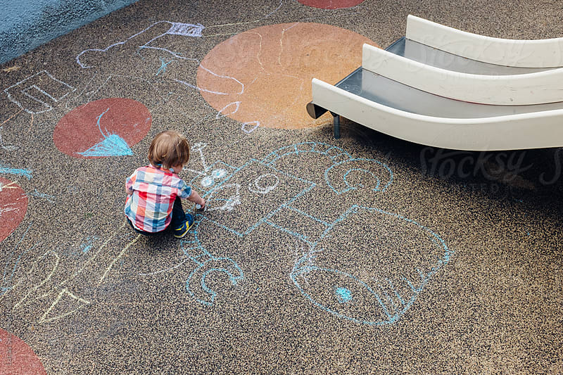 A young toddler at a playground drawing a chalk robot. by Lucas Saugen for Stocksy United