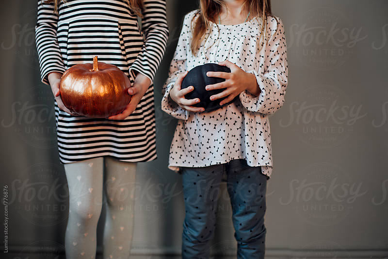 Girls Holding Pumpkins  by Lumina for Stocksy United
