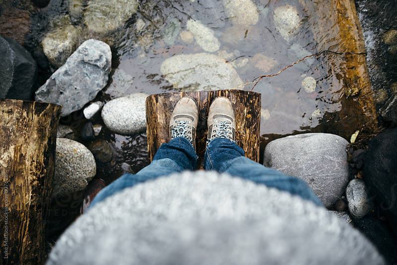 Man In Hiking Boots Standing At Edge Of Log Above River by Luke Mattson for Stocksy United