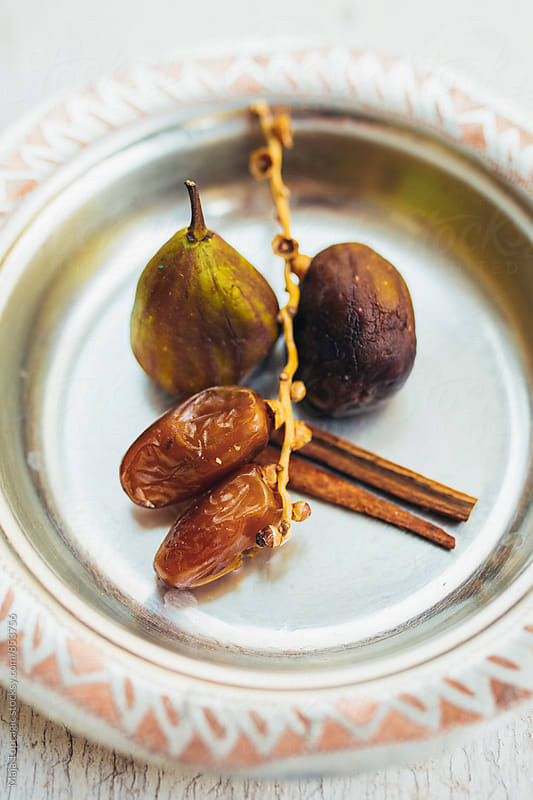 Fig, dates and cinnamon sticks on a plate by Maja Topcagic for Stocksy United