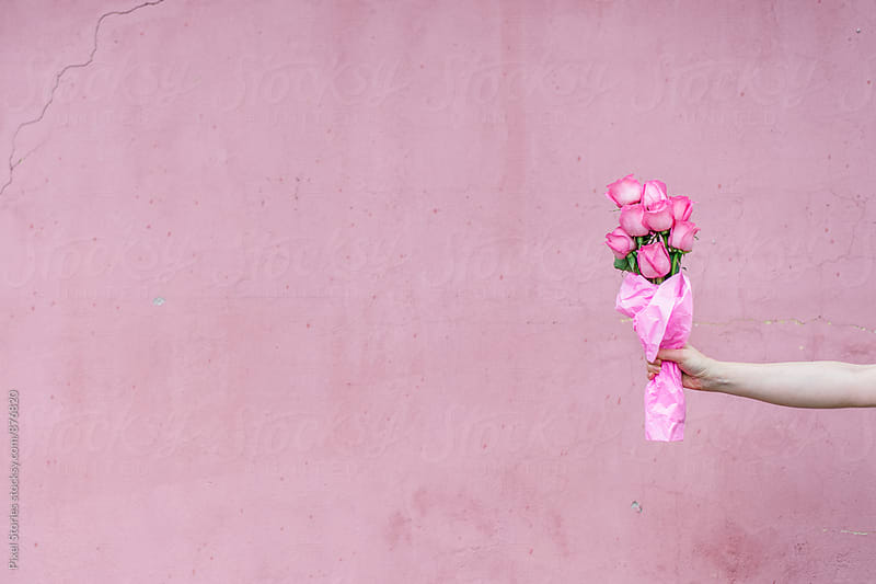 Woman holding a bouquet of pink roses by Pixel Stories for Stocksy United