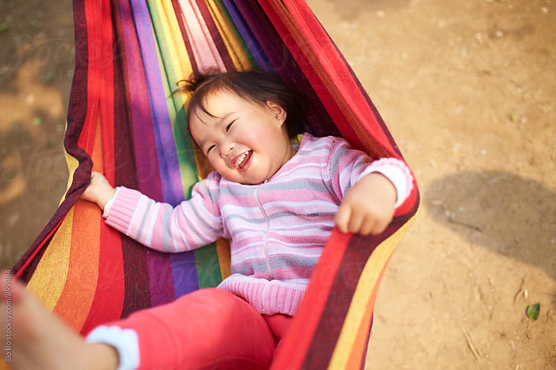 happy little asian girl in the hammock by Bo Bo for Stocksy United