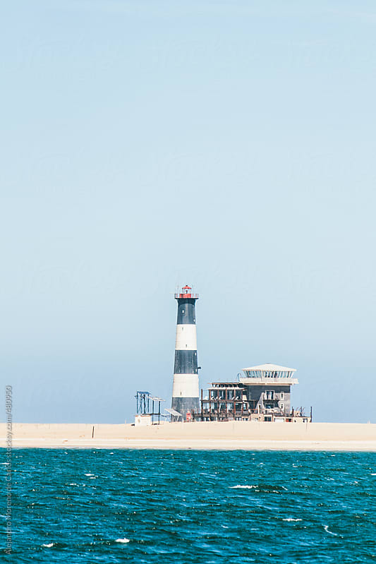 Lighthouse on a beach with copyspace by Alejandro Moreno de Carlos for Stocksy United