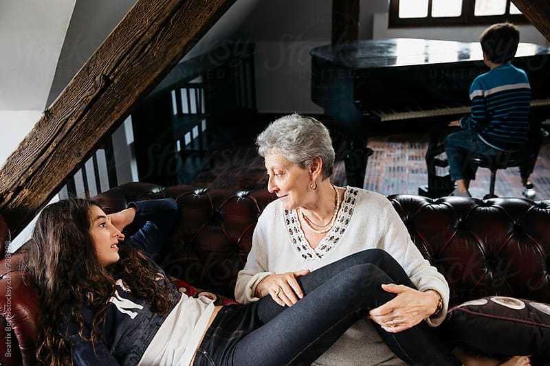 Grandmother talking to her granddaughter on the sofa by Beatrix Boros for Stocksy United
