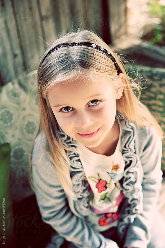 Young Blonde Hair, Blue Eyed Girl, Looking Up At The Camera by Leigh Love for Stocksy United