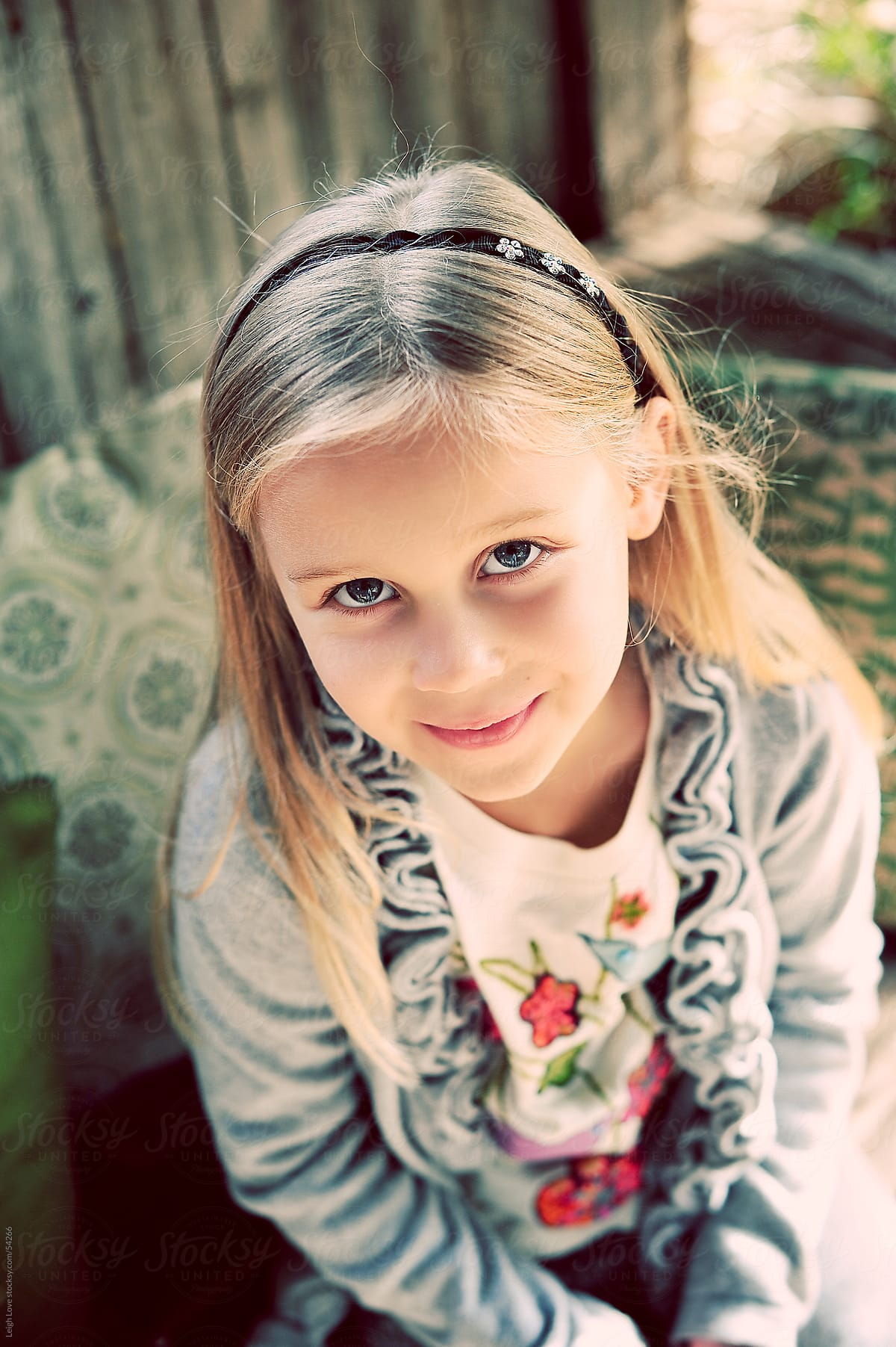 young blonde hair blue eyed girl looking up at the camera