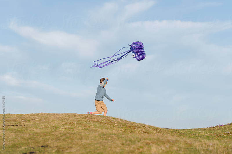 Happy child running with airborne kite by Rebecca Spencer for Stocksy United