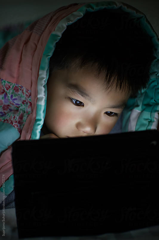 Asian kid playing with tablet computer in bed at home by Suprijono Suharjoto for Stocksy United