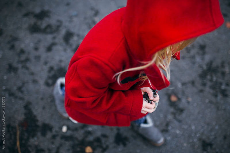 View From Above Of A Little Girl Walking in Her Bright Red Coat by Amanda Voelker for Stocksy United