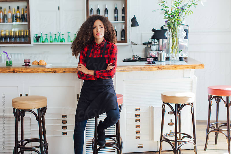 Portrait of a young curly waitress in a restaurant.  by BONNINSTUDIO for Stocksy United