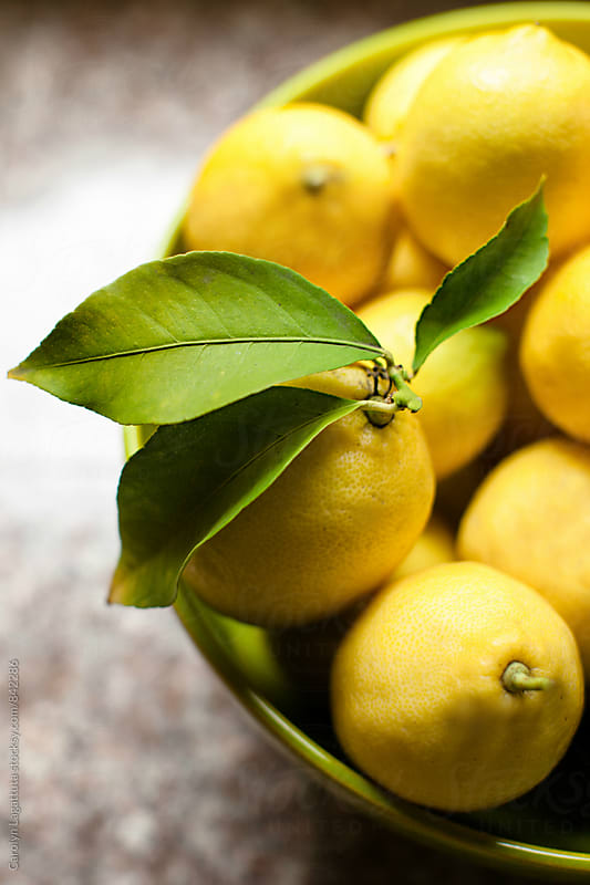 Large bowl of organic lemons by Carolyn Lagattuta for Stocksy United