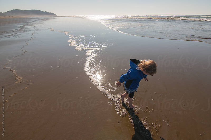 little girl explores the beach by Margaret Vincent for Stocksy United