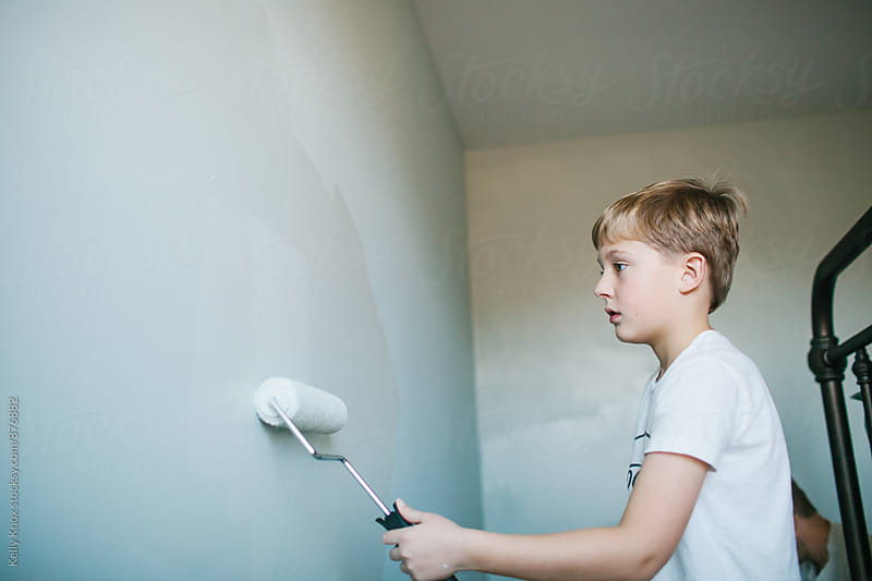 boy using a paint roller to paint his bedroom  by Kelly Knox for Stocksy United