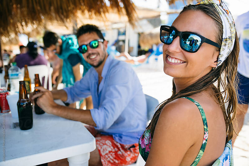 Young woman and man enjoying beers in a beach bar on a tropical location with their friends by Alejandro Moreno de Carlos for Stocksy United