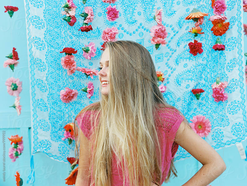 blonde girl in front of hanging pink flowers and blue background by wendy laurel for Stocksy United